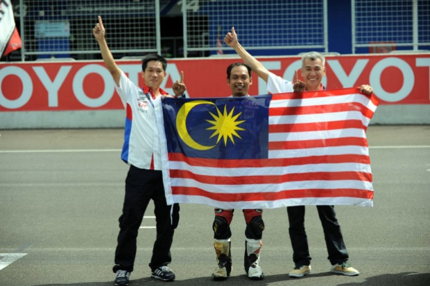 Norizman Ismail and team manager Soong Chee Kieong with the Malaysian flag in Thailand